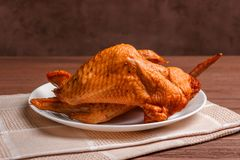 熏制的鸡翅用在一块白色板材的香料在餐巾 免版税库存照片