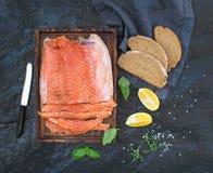 熏制鲑鱼内圆角用柠檬,新鲜的草本和养殖在黑暗的石背景的木服务板 免版税库存照片