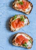 熏制鲑鱼和乳脂干酪三明治 在蓝色背景,顶视图 可口开胃菜用酒 图库摄影