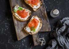 熏制鲑鱼和乳脂干酪三明治 在黑暗的背景的一个土气木切板上,顶视图 可口的开胃菜 免版税库存照片