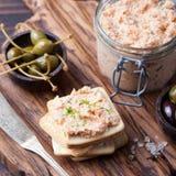 熏制鲑鱼和软干酪传播、奶油甜点、头脑在一个瓶子用薄脆饼干和雀跃在木背景 免版税图库摄影