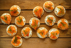 熏制鲑鱼和软的chees点心开胃菜用香葱在木桌上 免版税图库摄影