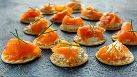 熏制鲑鱼和软的chees点心开胃菜用香葱在石桌上 免版税库存图片