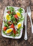 熏制鲑鱼,鸡蛋,芝麻菜,红洋葱,橄榄油,柠檬穿戴在木背景的沙拉 库存照片
