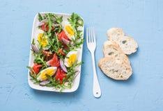 熏制鲑鱼,鸡蛋,芝麻菜,红洋葱,橄榄油,柠檬穿戴在蓝色背景,顶视图的沙拉 免版税库存图片