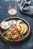熏火腿、甜瓜瓜、无盐干酪乳酪和玻璃上升了 免版税库存照片