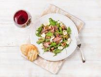 熏火腿、芝麻菜、无花果红色沙拉用面包和玻璃  免版税库存图片