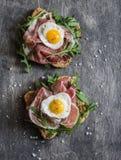 熏火腿、芝麻菜和油煎的鹌鹑蛋三明治 可口早餐、快餐或者开胃菜 免版税库存图片