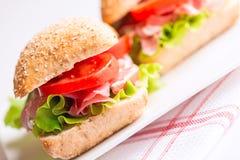 熏火腿三明治用蕃茄和芝麻菜在板材 免版税库存照片