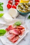 熏火腿橄榄橄榄油无盐干酪乳酪蕃茄蓬蒿-意大利语的成份或地中海烹调 免版税库存图片
