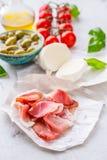 熏火腿橄榄橄榄油无盐干酪乳酪蕃茄蓬蒿-意大利语的成份或地中海烹调 免版税库存照片