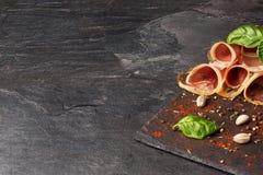 熏火腿特写镜头  被切的jamon用菠菜和开心果在深灰背景 餐馆开胃菜 复制 免版税库存照片