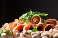熏火腿特写镜头  被切的jamon用菠菜和开心果在黑背景 美丽的餐馆开胃菜 免版税库存图片