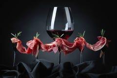 熏火腿用迷迭香和杯在一黑暗的backgro的红葡萄酒 库存照片