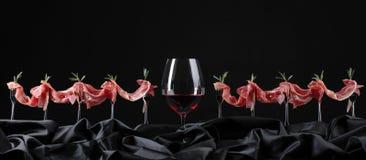 熏火腿用迷迭香和杯在一黑backgr的红葡萄酒 免版税库存图片