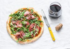 熏火腿芝麻菜自创薄饼和一杯在轻的背景,顶视图的红葡萄酒 可口的开胃菜 免版税图库摄影