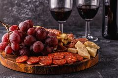 熏火腿,香肠,酒,葡萄,在黑暗的桌上的巴马干酪 免版税库存图片