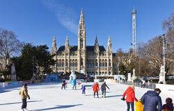 熏肉香肠的Eistraum -在维也纳市政厅前面的滑冰场滑冰的人 库存图片
