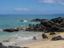 熔岩岩石和珊瑚与碰撞的波浪浪花在浪潮水池在Maluaka海滩和Kihei毛伊与天空和云彩 库存照片