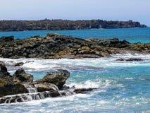 熔岩岩石和珊瑚与碰撞的波浪浪花在浪潮水池在Maluaka海滩和Kihei毛伊与天空和云彩 免版税图库摄影