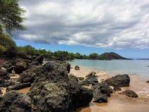 熔岩岩石和珊瑚与碰撞的波浪浪花在浪潮水池在Maluaka海滩和Kihei毛伊与天空和云彩 库存图片