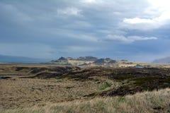 熔岩荒野在冰岛在西部海湾区域在遥远的山和风雨如磐的天空背景  库存照片