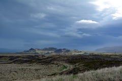 熔岩荒野在冰岛在西部海湾区域在遥远的山和风雨如磐的天空背景  库存图片