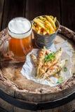 熔炼在老桶的鱼用冰镇啤酒和芯片 库存图片