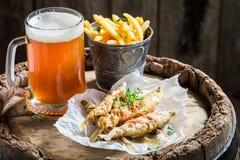 熔炼炸鱼加炸土豆片用在老桶的冰镇啤酒 免版税库存照片