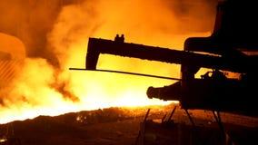 熔融金属倾吐从特别机制的,冶金学概念 流动在冶金滑道的溶解的钢后边 免版税库存照片