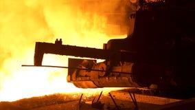 熔融金属倾吐从特别机制的,冶金学概念 流动在冶金滑道的溶解的钢后边 免版税图库摄影