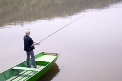 熔铸A从绿色小船的钓鱼竿在湖和耐心地等待鱼的渔夫采取诱饵 免版税库存照片