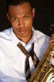熟悉内情的萨克斯管吹奏者年轻人 免版税图库摄影