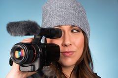 熟悉内情的年轻成年女性指向拍电影的摄象机 免版税库存照片