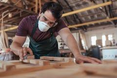熟练地铺沙木头的年轻工匠在他的大车间 免版税库存图片