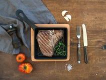 熟肉丁骨牛排用拨蒜、蕃茄、迷迭香、胡椒和盐在小烹调平底锅在土气木 库存图片