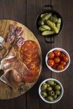 熟食店和塔帕纤维布盘的选择在一张木桌上的 免版税库存照片