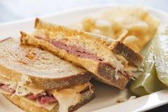 熟食店样式Reuben三明治用腌汁和土豆片 免版税图库摄影