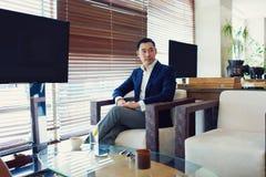 熟练的商人在有拷贝空间的屏幕附近坐您的内容的 图库摄影