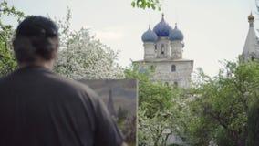 熟练的艺术家在开花的庭院2里画油漆寺庙 股票录像