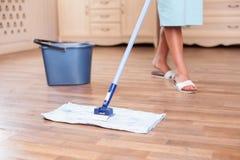熟练的年轻主妇清洗地板与a 库存照片