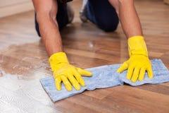 熟练的年轻擦净人在房子里擦地板 免版税库存照片