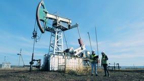 燃料抽油井架和两位审查员谈话在它附近 股票录像