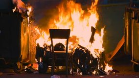 燃烧的垃圾容器和老木椅子与其他垃圾关闭 塑料垃圾箱几乎熔化了 股票视频