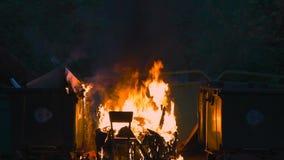 燃烧的垃圾容器和老木椅子与其他垃圾关闭 塑料垃圾箱几乎熔化了 影视素材