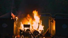 燃烧的垃圾容器和老木椅子与其他垃圾关闭 塑料垃圾箱几乎熔化了 股票录像