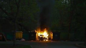 燃烧的垃圾容器和老木椅子与其他垃圾 塑料垃圾箱几乎熔化了 股票录像