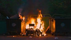 燃烧的垃圾容器和老木椅子与其他垃圾 塑料垃圾箱几乎熔化了 影视素材