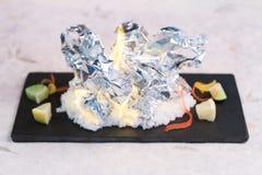燃烧的烤蛤蜊由箔,与盐的烧伤的套服务与在黑长方形板材的被切的石灰在washi日文报纸 库存图片