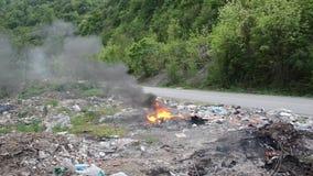 燃烧的狂放的垃圾堆 塑料袋、瓶、垃圾和垃圾在河附近 沉重污染的河岸 环境波尔布特 股票录像